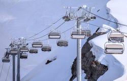 Vakanta cablewayelevatorstolar av ett tomt skidar semesterorten på den soliga vinterdagen mot snöig bakgrund för berglutningar Royaltyfri Fotografi