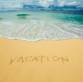 Vakantie die in een zandig strand wordt geschreven Stock Foto's