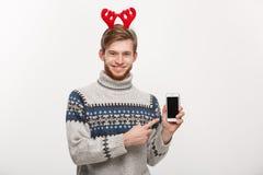 Vakantie en Bedrijfsconcept - Jonge knappe mens die mobiele telefoonvertoning tonen en vinger het voorstellen richten royalty-vrije stock foto's