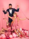 vakantie en poppen overheersing en afhankelijkheid Gekke meisjes en mens op roze Halloween de uitstekende marionet van maniervrou royalty-vrije stock foto's