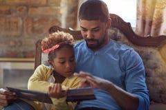 Vakantie en vieringsconcept - Vader en dochter de sprookjes van lezingskerstmis stock foto