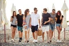 vakantie, vakantie groep die vrienden die pret op strand hebben, drinkt bier, het glimlachen en het koesteren de lopen royalty-vrije stock afbeeldingen