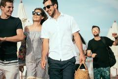 vakantie, vakantie groep die vrienden die pret op strand hebben, drinkt bier, het glimlachen en het koesteren de lopen stock fotografie