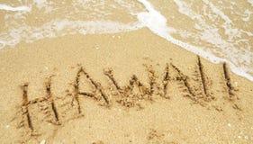 Vakantie in Hawaï in zand wordt geschreven dat Stock Afbeelding