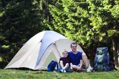Vakantie het Kamperen Vader en zijn zoon die rust daarna nemen dichtbij tent Royalty-vrije Stock Afbeeldingen