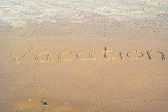 Vakantie in het zand wordt geschreven dat Royalty-vrije Stock Afbeeldingen