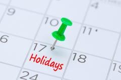 Vakantie op een kalender met een groene duwspeld wordt geschreven om y eraan te herinneren dat Stock Foto