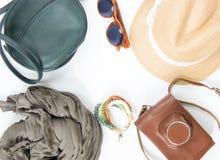 Vakantie, reisachtergrond Groene dwarszak, strohoed, retro bruine zonnebril, grijze sjaal, retro camera, bochoarmband Stock Foto's