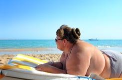 Vakantie - te zware vrouw op strand Stock Afbeeldingen