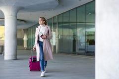 Vakantie, toerisme en reisconcept - jonge vrouwentoerist die met koffer en paspoort in luchthaven of post lopen stock afbeelding