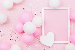 Vakantie of verjaardagsmodel met kader, pastelkleurballons, hart en confettien op de roze mening van de lijstbovenkant Vlak leg s royalty-vrije stock afbeelding