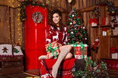 Vakantie, viering en mensenconcept - jonge glimlachende vrouw in rode Kerstmisgift van de sweaterholding over Kerstmisbinnenland stock afbeeldingen