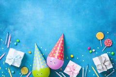 Vakantieachtergrond met grappige ballons in kappen, giften, confettien, suikergoed en kaarsen Vlak leg Verjaardag of de kaart van stock foto