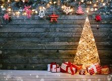 Vakantieachtergrond met verlichte Kerstboom, giften en D Stock Foto