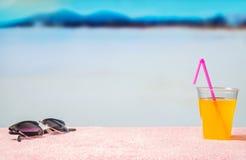 Vakantieachtergrond met vrije lege exemplaarruimte Zonnebril en gele cocktail met roze stro op strand Royalty-vrije Stock Afbeelding