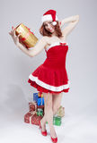 Vakantieconcept en Ideeën Gelukkige Glimlachende Kaukasische Rode Haired Santa Helper Holding Golden Gift ter beschikking royalty-vrije stock foto's