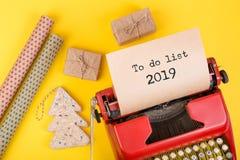 Vakantieconcept - rode schrijfmachine met tekst & x22; Om lijst 2019& x22 te doen; , giftvakjes en verpakkend document stock foto