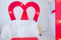 Vakantiedecoratie voor de huwelijksscène in de vorm van karmozijnrode harten Bank voor de bruid en de bruidegom Royalty-vrije Stock Fotografie