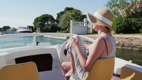 Vakantiedromen in Europa Vrouw in zonnebril en hoed die in een kleine boot in Empuriabrava, Spanje drijven stock videobeelden