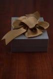 Vakantiegift in Grey Box met Lint op Glanzend Houten T wordt ingepakt dat Royalty-vrije Stock Afbeelding