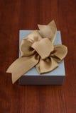 Vakantiegift in Grey Box met Lint op Glanzend Houten T wordt ingepakt dat Royalty-vrije Stock Foto's