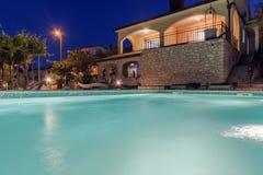 Vakantiehuis met zwembad bij nacht stock fotografie