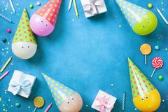 Vakantiekader of achtergrond met grappige ballons in kappen, giften, confettien, suikergoed en kaarsen Vlak leg Verjaardag of par Royalty-vrije Stock Fotografie