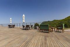 Vakantielijsten, stoelen, een bank en gesloten paraplu's op de portiek Stock Foto