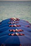 Vakantieseizoen - vele strandparaplu's op de overzeese strandzonsondergang royalty-vrije stock afbeelding