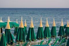 Vakantieseizoen - vele strandparaplu's op de overzeese strandzonsondergang stock fotografie