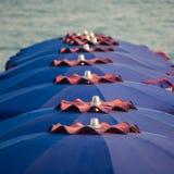Vakantieseizoen - vele strandparaplu's op de overzeese strandzonsondergang royalty-vrije stock foto