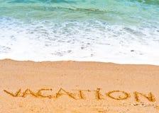 Vakantiewoord in het zand op de strand blauwe golven wordt geschreven op de achtergrond die stock foto