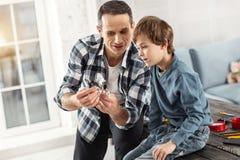 Vaken fader som visar hans instrument till hans son Arkivbilder