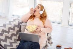 Vaken fet kvinna som äter mycket popcorn royaltyfria foton