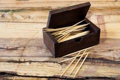 Vakje van tandenstokers op houten lijst Stock Foto
