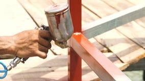 Vakman die spuitpistool voor het toepassen van bruine verf op metaaldelen gebruiken Arbeider het schilderen metaalomheining met v stock footage
