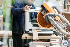 Vakmanhoutbewerking bij timmerwerk met veel moderne professionele machtshulpmiddelen Mens die thicknessing machine met behulp van royalty-vrije stock fotografie