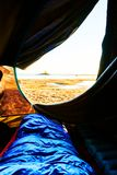 Vakna upp under soluppgång Sikt ut ur ett tält på stranden som ser sanden och vattnet i Sverige I förgrunden finns det fotografering för bildbyråer
