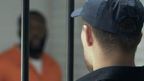 Vakt som sköter den extremt farliga fången i cell för dom stock video