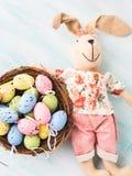 Vakteln för dockan för påskkaninen målade bakgrunden för äggredepastell Fotografering för Bildbyråer
