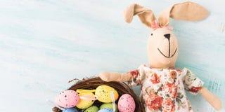 Vakteln för dockan för påskkaninen målade bakgrunden för äggredepastell Arkivbilder
