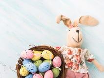 Vakteln för dockan för påskkaninen målade bakgrunden för äggredepastell Arkivfoton