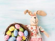 Vakteln för dockan för påskkaninen målade bakgrunden för äggredepastell Royaltyfri Foto