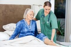 Vaktmästare som undersöker höga kvinnas ben royaltyfria foton