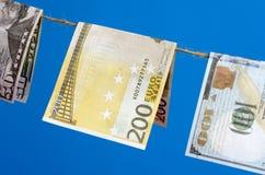 Valörer av dollar och euro på en kabel på pinnor Royaltyfri Fotografi