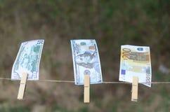 Valörer av dollar och euro på en kabel på pinnor Arkivbild