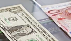 Valörer av en dollar och tio euro ligger på scaner Arkivfoton