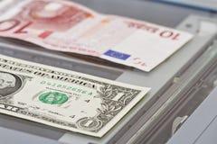 Valörer av en dollar och tio euro ligger på scaner Royaltyfri Foto