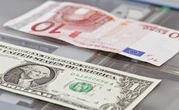 Valörer av en dollar och tio euro ligger på scaner Royaltyfri Bild