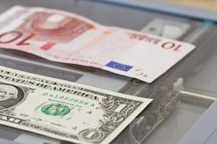 Valörer av en dollar och tio euro ligger på scaner Royaltyfria Foton
